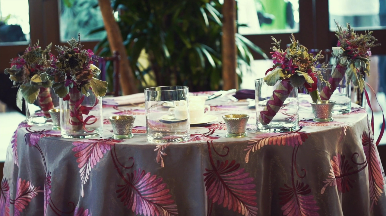The Head Table is Decorated with a Purple Patterend Tablecloth and Round Vases